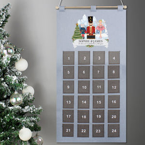 Personalised reuseable advent calendar made from grey felt with 24 individual pockets. The calendar has a wooden pole across the top attached to a length of string so it can be hung up. An image of a toy wooden nutcracker is printed at the top aong with a hand drawn mouse and a fairy ballerina all standing in a festive snow scene. The calendar can be printed with two lines of text, the first line will be printed in a large uppercase font and the second line in a smaller cursive font.