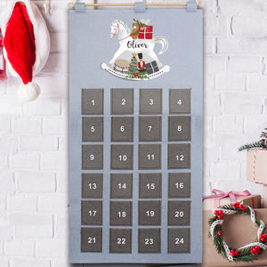 Personalised grey felt reuseable advent calendar with 24 individually numbered pockets. The calendar can be hung via a string at the top of the advent calendar.  Above the pockets there is an image of a hand-drawn white rocking horse and the calendar can be personalised with a name of your choice of up to 12 characters which will be printed in a modern cursive black font on the body of the rocking horse.
