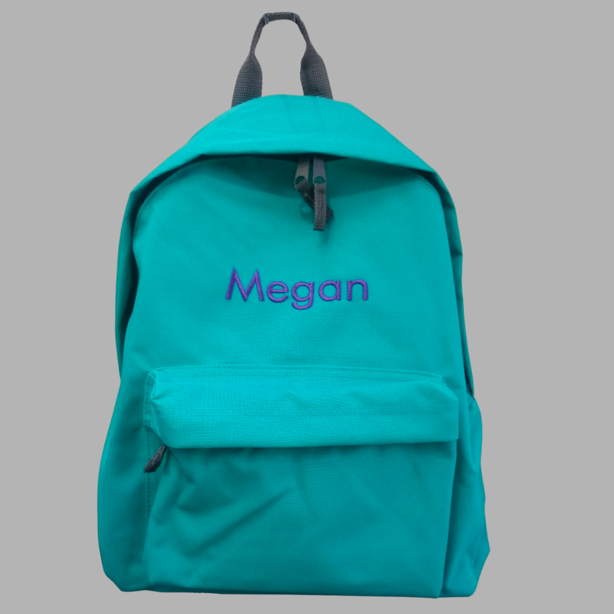 Personalised school rucksack in emerald green with grey zips and trim with our modern font choice.  The rucksack is embroidered with a name of your choice in a colour of your choice.