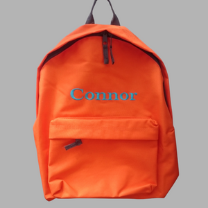 Personalised school rucksack in orange with grey zips and trim with our traditional font choice. The rucksack is embroidered with a name of your choice in a colour of your choice.