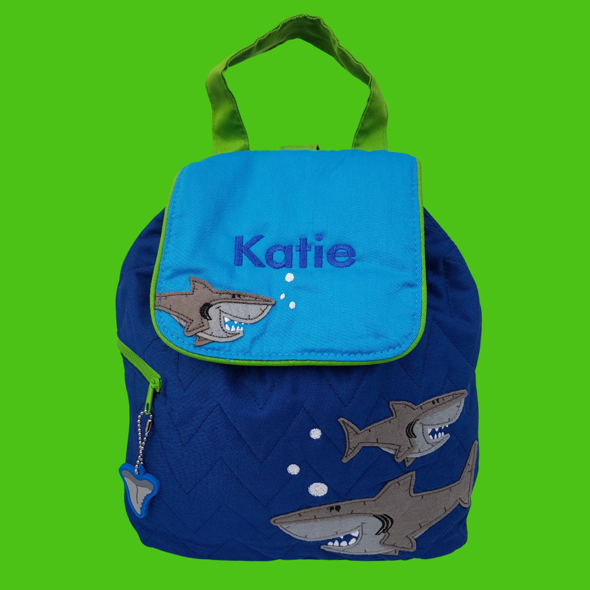 Personalised Stephen Joseph shark child's backpack made from royal blue quilted fabric with a grey shark design on the front. The opening flap which is mid blue can be embroidered with a name of your choice.