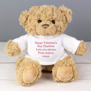 Image of a personalised traditional teddy bear with soft light brown fur sitting down. The teddy is wearing a white jumper that can be personalised with your own message over up to 5 lines in your choice of grey, pink or blue.