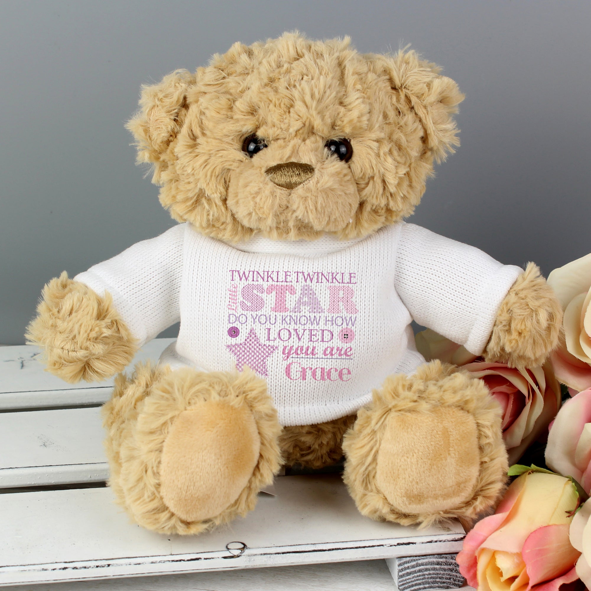 Image of a light brown soft traditional teddy bear wearing a white jumper with the text 'twinkle twinkle little star, do you know how loved you are' printed on it in a mixture of fonts and different shades of pink and purple text. You can then add a name of your choice which will be printed in pink after the fixed text.