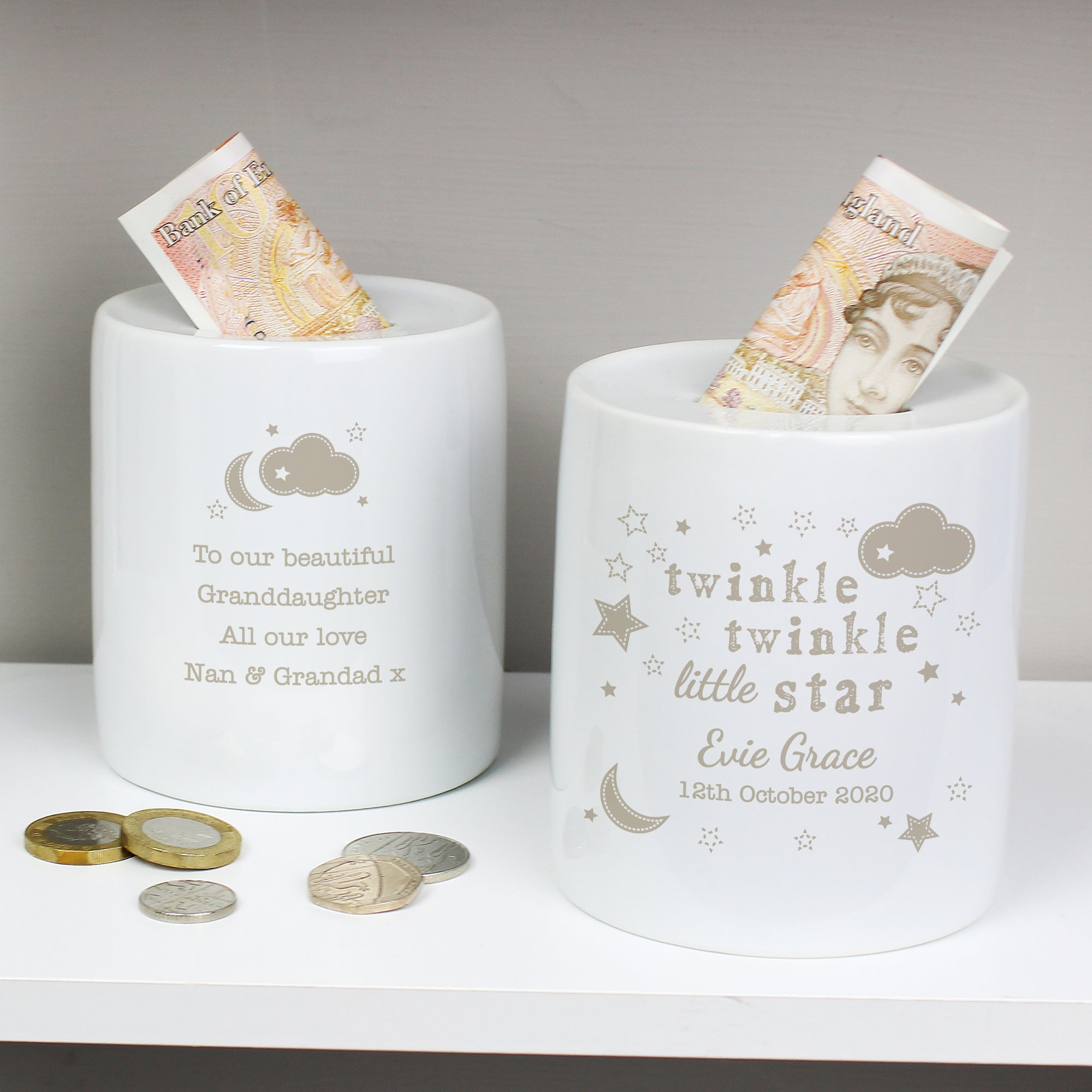 Image of a personalised ceramic money box. The money box is a white cylinder with a money slot on the top. The front of the money box features the text 'twinkle twinkle little star' in a mixture of fonts and below this you can add a name and date of your choice.  The back of the money box features an image of a crescent moon and a cloud and below this you can add your own message over up to 4 lines.  All of the text and images are printed in a dark beige colour.
