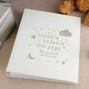 Personalised photo album with a cream satin finished front cover and the words 'twinkle twinkle little star' printed on the front along with some illustrations of stars and clouds printed in a dark sand colour. The front of the album can be personnalised with a name and date which will be printed in the same colour. Inside the album has 25 double-sided sleeved pages which can hold one or two photos depending on their size.