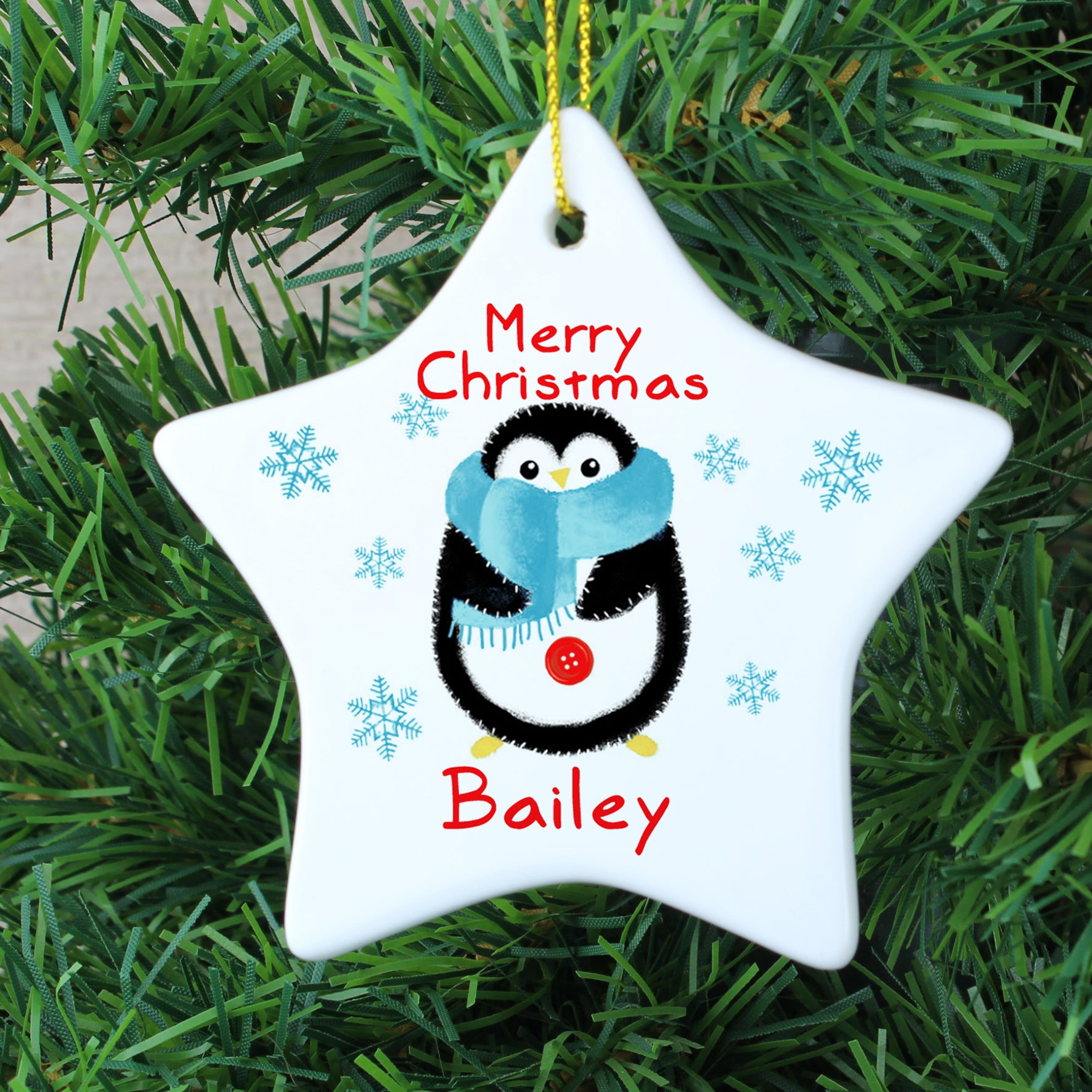 Personalised white ceramic Chrismas star decoration featuring the words 'Merry Christmas' in a red font and an image of a hand drawn penguin wearing a blue scarf. The decoration can be personalised with a name in red which will be printed below the image of the penguin.