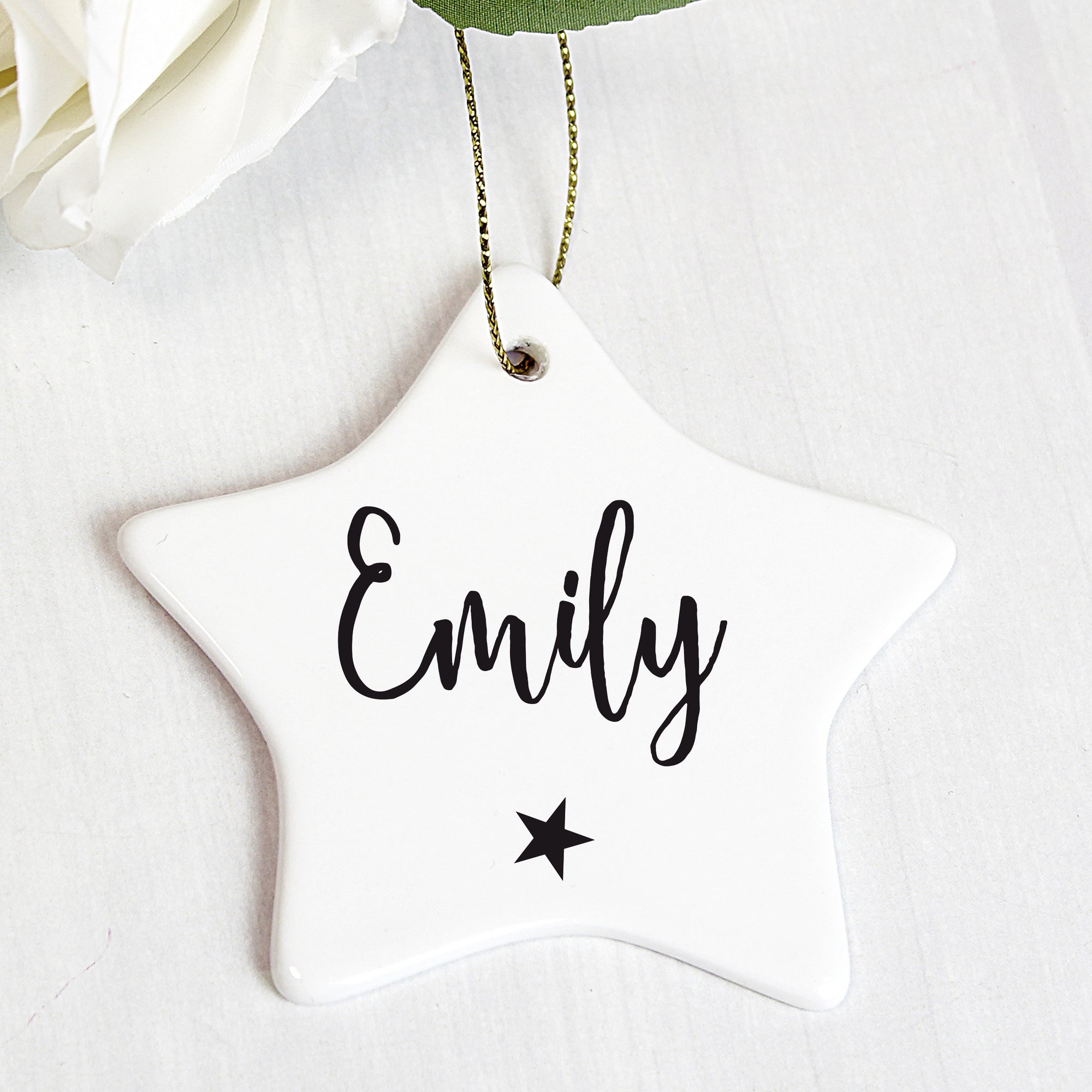 Personalised white ceramic star shaped Christmas decoration that comes with a string ready to hang. The front of the decoration can be personalised with a name of up to 12 characters which will be printed in a black modern hand written style font and there is a small black star printed below the name.