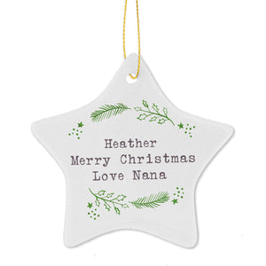 Personalised white ceramic star shaped Christmas decoration which has a green hand drawn design on it of pine fronds, holly and stars. The centre of the star can be personalised with your own text over up to 3 lines which is printed in a grey font. The decoration comes with a string making it ready to hang.