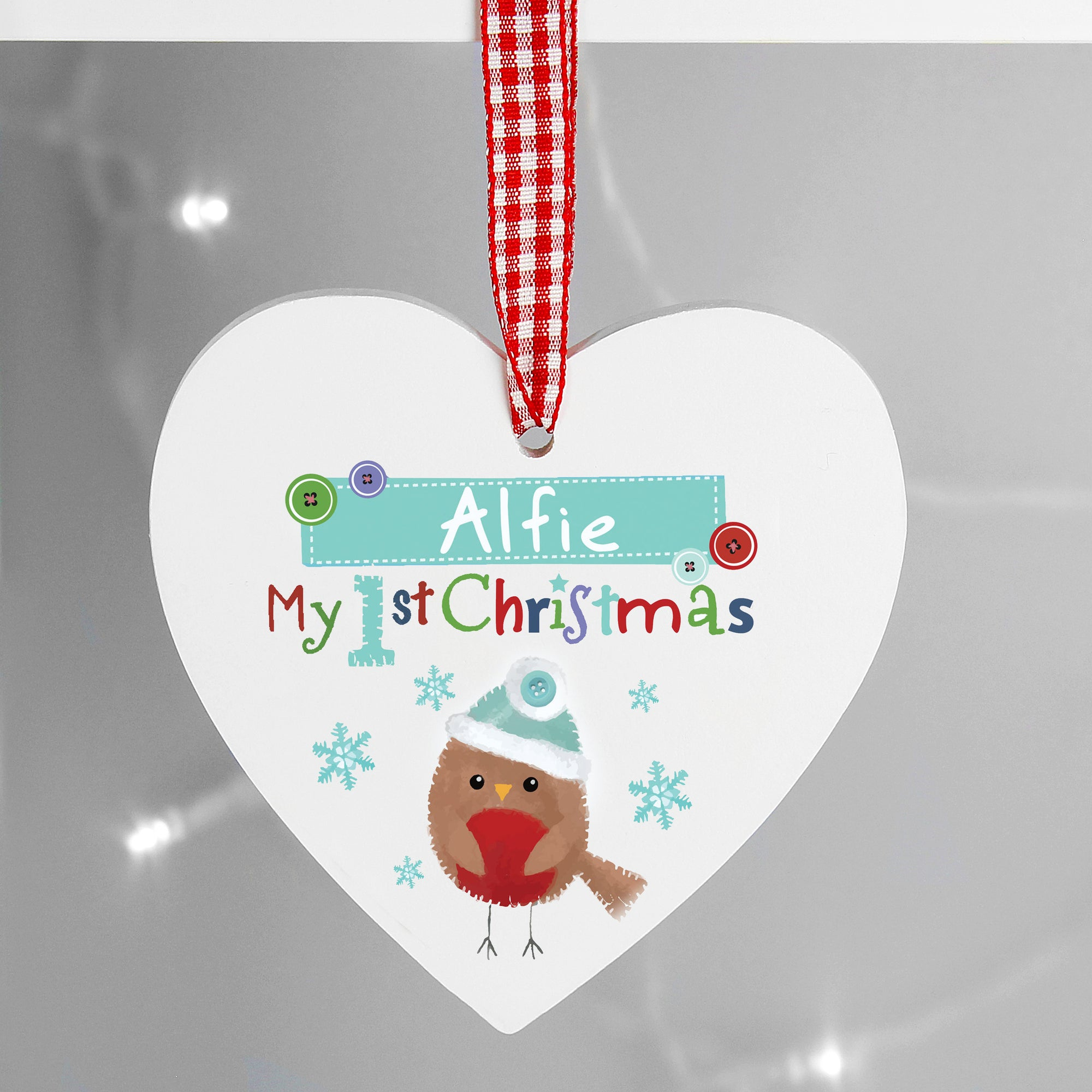 Personalised white wooden heart shaped Christmas decoration featuring an image of a hand-painted robin and the text 'My 1st Christmas' in bright letters.  The decoration can be personalised with a name of your choice up to 12 characters.