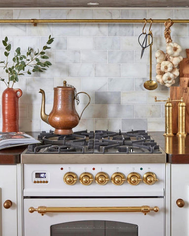 White and Gold cooker- Image of a Milano range cooker in the colour with with a brass finish.