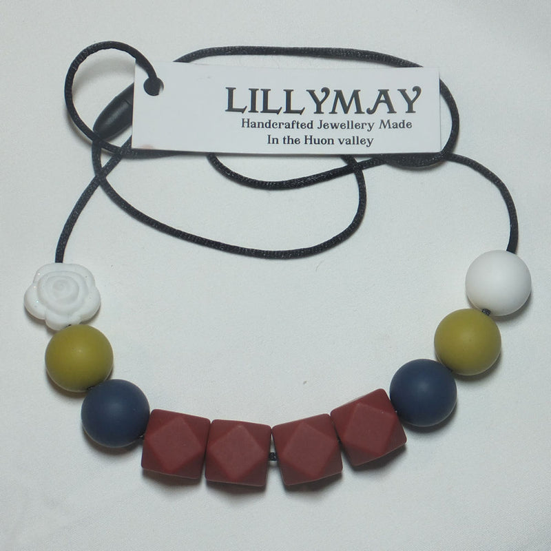 Necklace in Red hexagonal blocks, with Green and Blue beads with a single White bead complimented by a White rose emblem by LillyMay