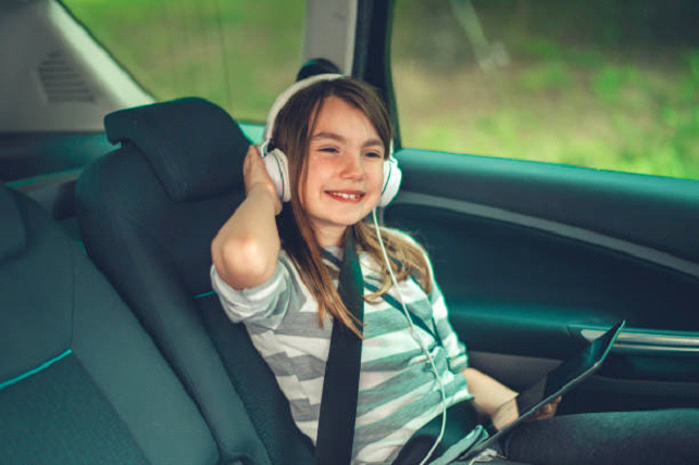 kid with headphones on in a car