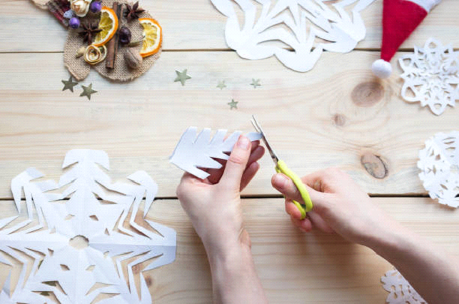 cutting out christmas paper snowflakes