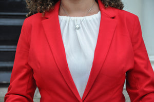 Girl's bust wearing a white shirt and red blazer and necklace with a Holy Spirit pendant and clear zirconias stones sits on a white rhodium-plated chain.