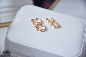Two pairs of Spike cubic zirconias hoop earring on top of a jewellery box