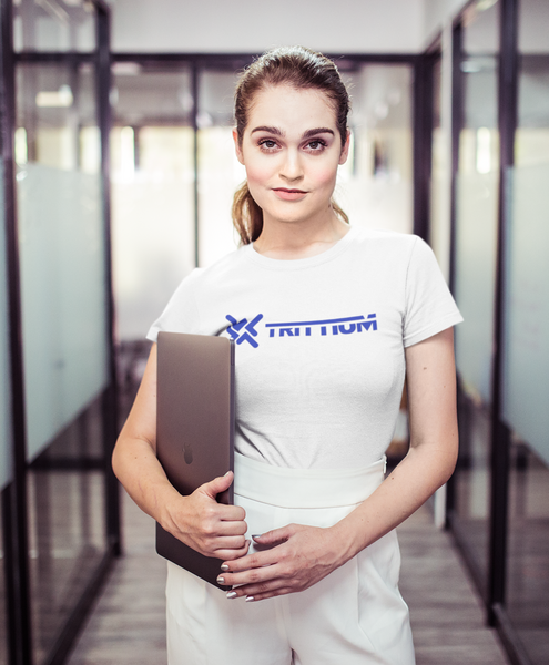 woman in office wearing trittium shirt while holding a laptop