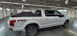 ford pickup with soft roll up expandable truck bed cover in garage