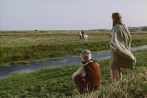 Two women stand in a field