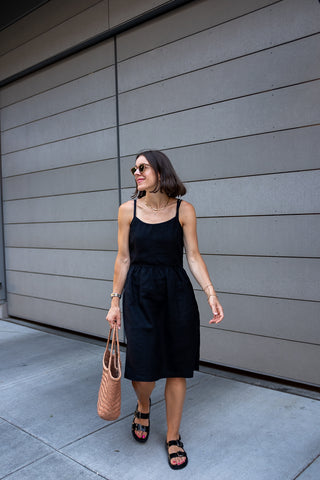 Seasons and Salt's Andrea wearing Pyne & Smith No. 34 dress in black linen with black sandals and a tan leather tote