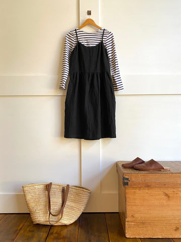 Pyne & Smith No. 34 dress in black linen layered over a long sleeve stripe top with leather mules and a tote