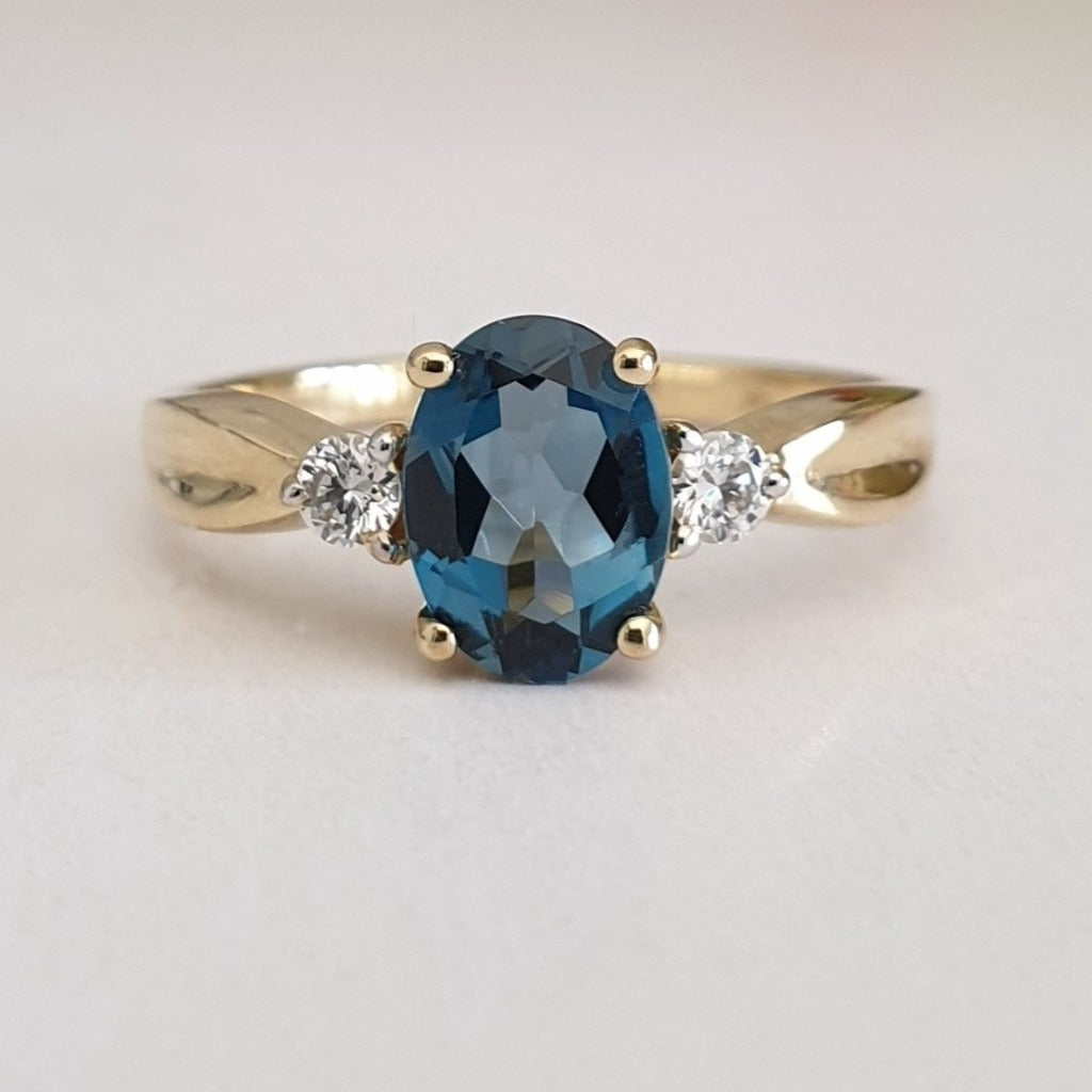 Oval-Cut London Blue Topaz Ring with Diamond Accents and Crimped Shoulder Detailing