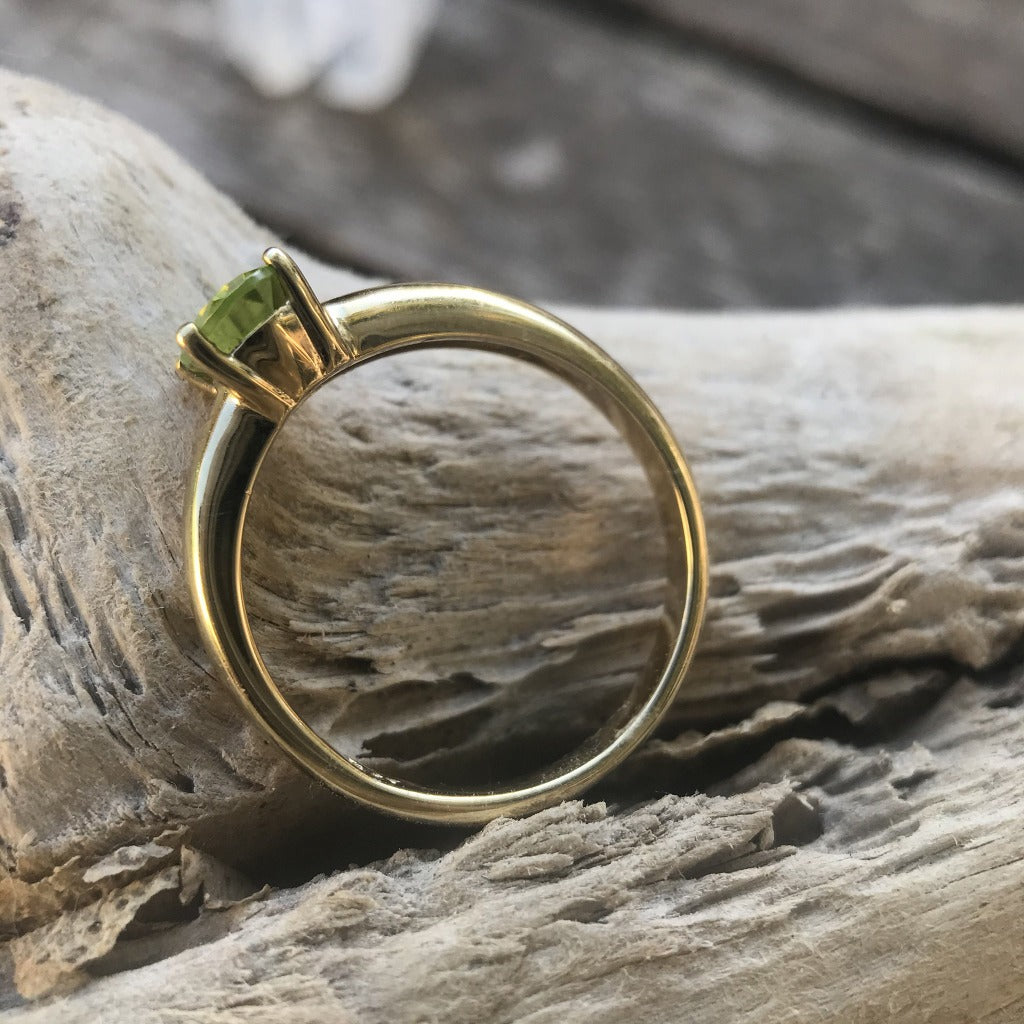 Oval Cut Peridot Solitaire Ring in a Four Claw Yellow Gold Setting
