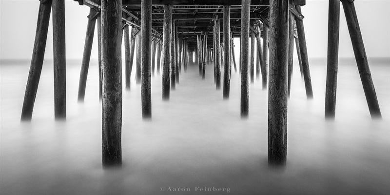Black and white photograph of underneath an old pier