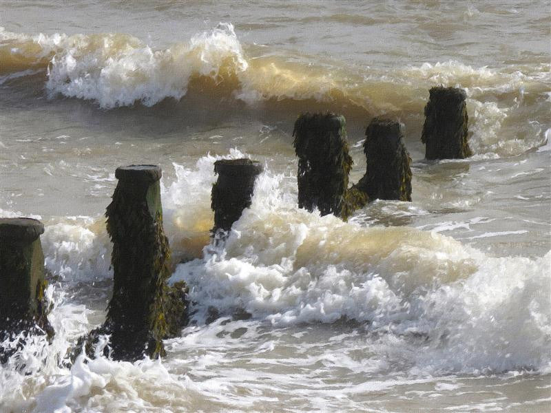 Seascape photograph of breakwaters rolling up a beach