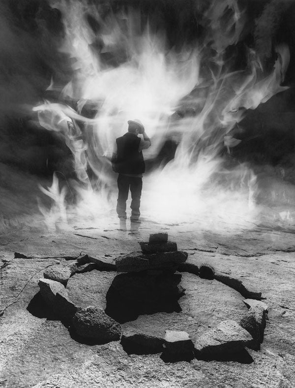 Surreal image of a man walking with fire in black and white