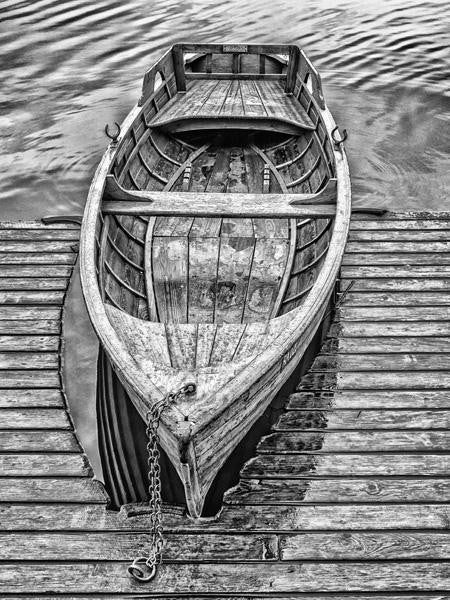 Stunning black and white photograph of a rowing boat at a pontoon