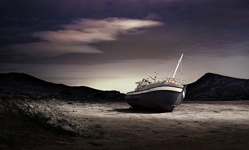 Photograph of a boat wreck leaning towards the water at night