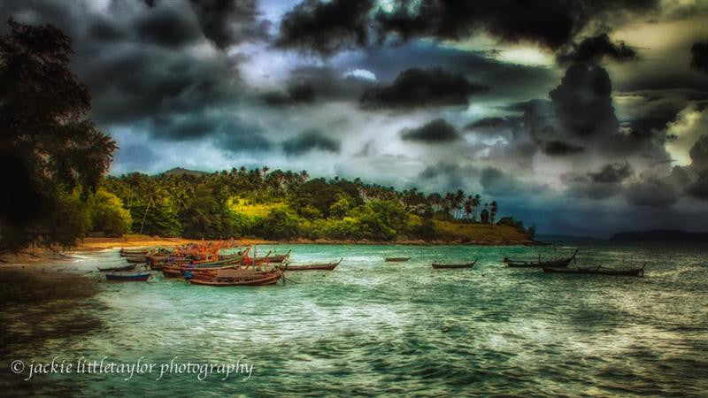 Storm coastline longtail boats dark clouds