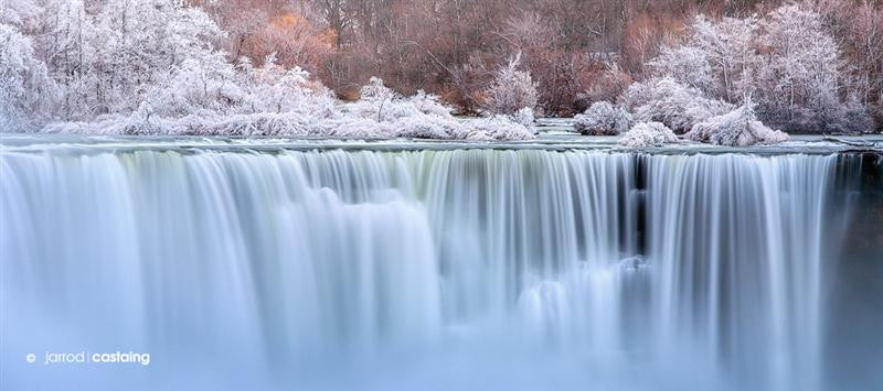 Long exposure photograph of a beautiful waterfall in winter with snow on the trees and ground