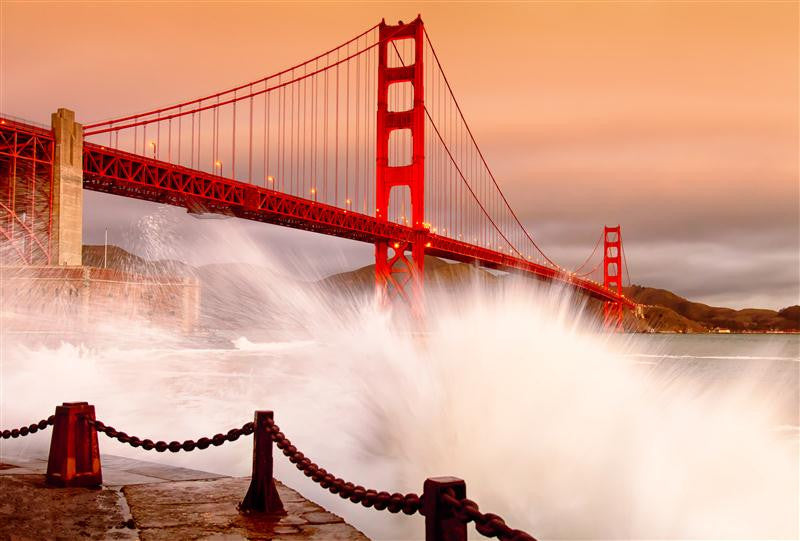 Waves crashing in the foreground with The Golden Gate Bridge gleaming in the sun