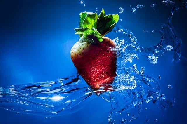 Abstract photograph of a strawberry falling into a bowl of fresh water