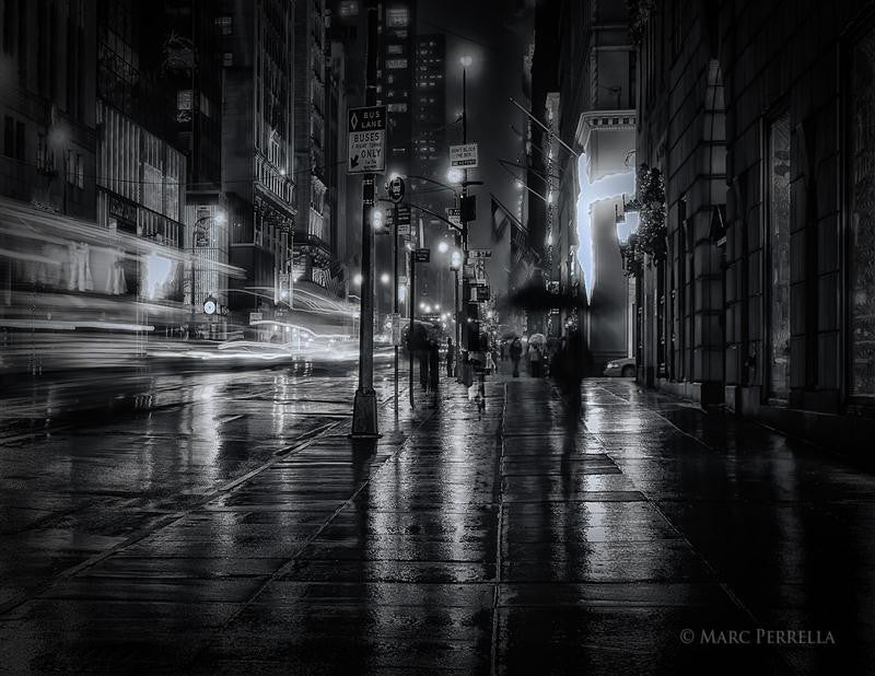 Black and white photograph of New York City in the rain at night