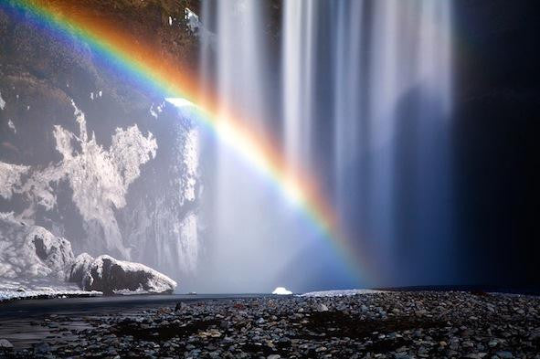 A colourful rainbow being made by the spray from the Kogafoss waterfall in Iceland