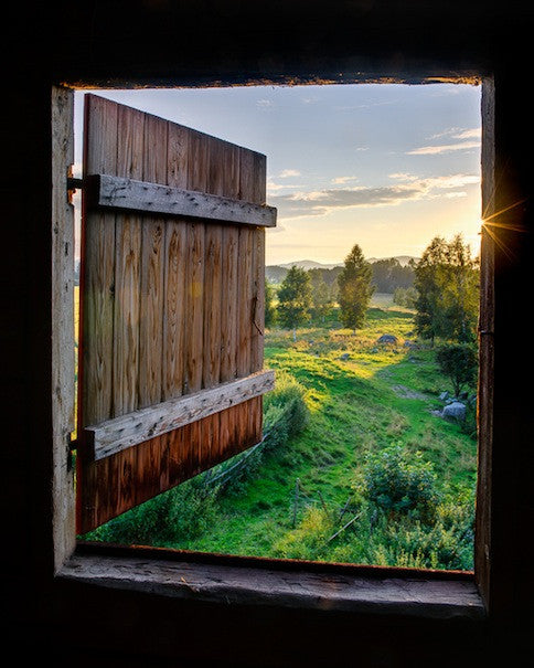 Landscape photograph of a sunset from a barn door
