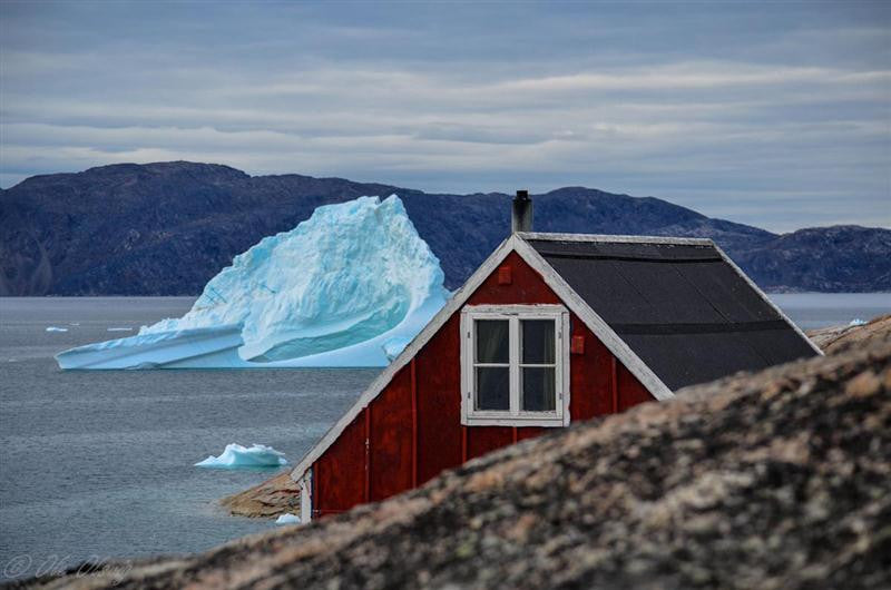 Photographic image of an iceberg floating past a cottage in Greenland