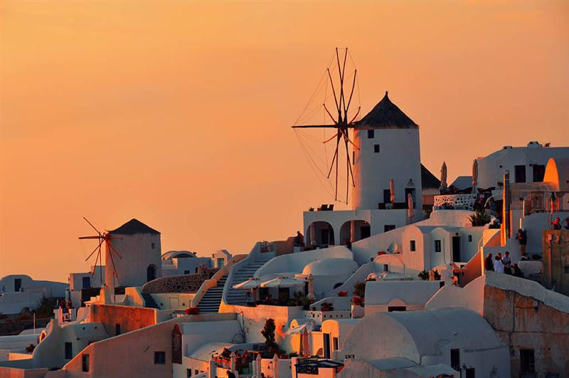 Stunning photograph of the windmills of Oia as the sun rises