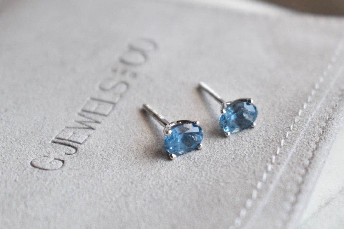 Oval Blue Topaz Stud Earrings in 14K White Gold