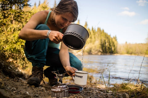 A hiker pours water from a Primus pot into a mug by a lake.