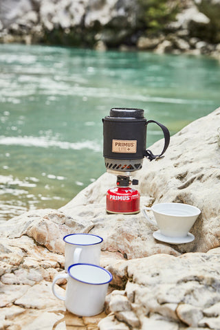 Primus Lite+ stove sits atop rocks on a riverbed.