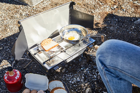 A shot of an outdoor cooking station setup shows eggs and toast on a stove in the wilderness.