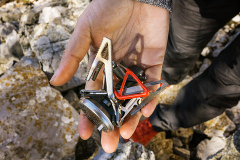 Camper holds a Primus backpacking stove folded up in their palm.