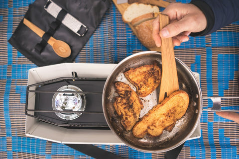 A camper prepares an easy camping meal over a Primus stove.