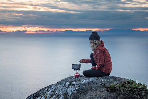 Camper sits overlooking the water, cooking on a Primus stove