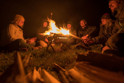 Group of friends gather around a fire.
