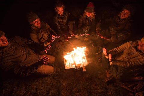 Group gathers around a Primus stove fire