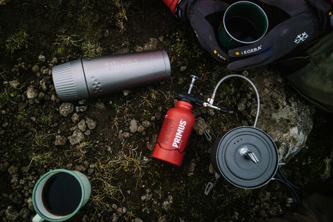 Primus canister and stove materials lay on a camping backdrop.
